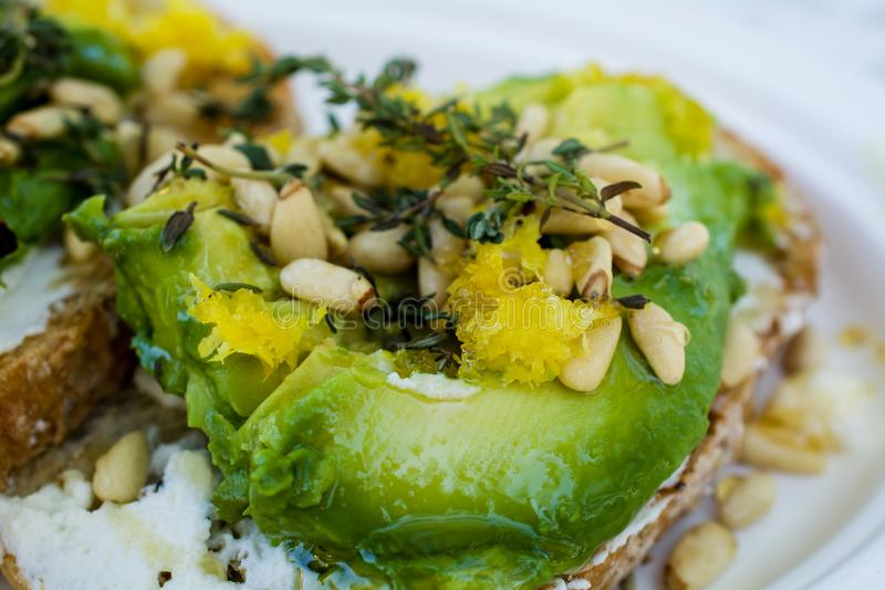 Avocado toast with pine nuts. Closeup on gourmet Mexican avocado toast garnished with cream cheese, lemon zest, pine nuts, and rosemary, on white plate stock photos