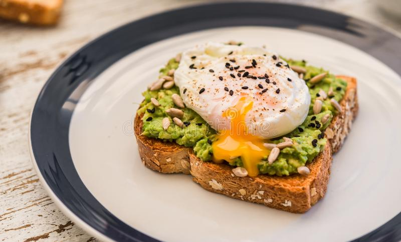 Avocado toast with poached egg. Vegetarian food and healthy eating concept. royalty free stock photo