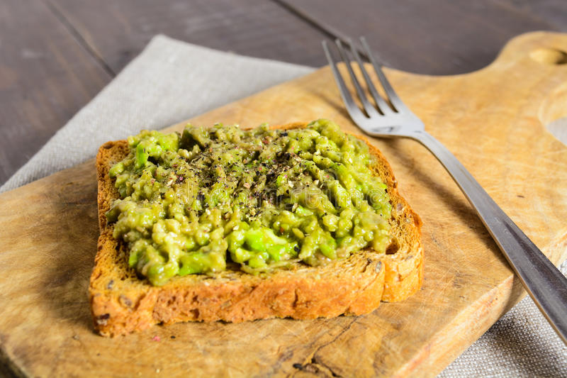 Avocado toast on wooden board stock photography