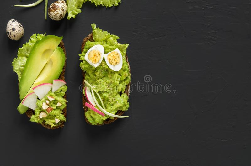 Avocado toasts on rye bread with sliced avocado for healthy breakfast on dark black stone background. Vegetarian food. Top view, stock images