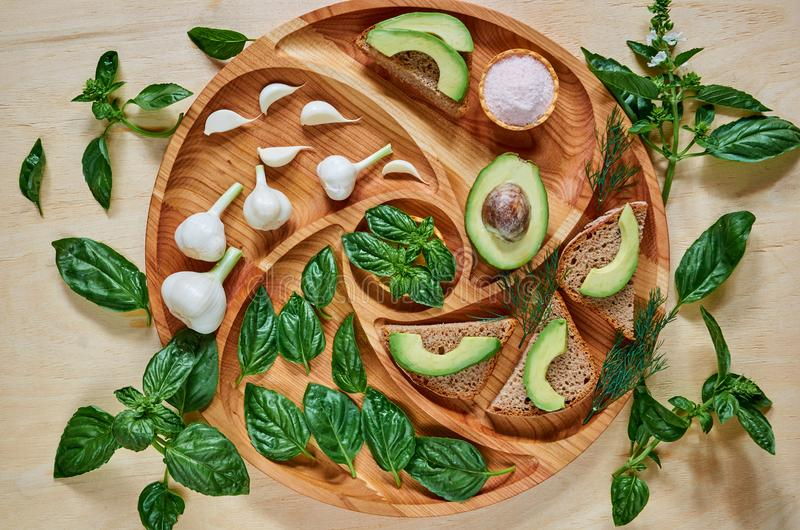 Avocado toasts on the wooden plate with garlic, basil, dill and salt. Vegan avocado sandwiches decorated with green basil leaves. On the wooden background stock photos