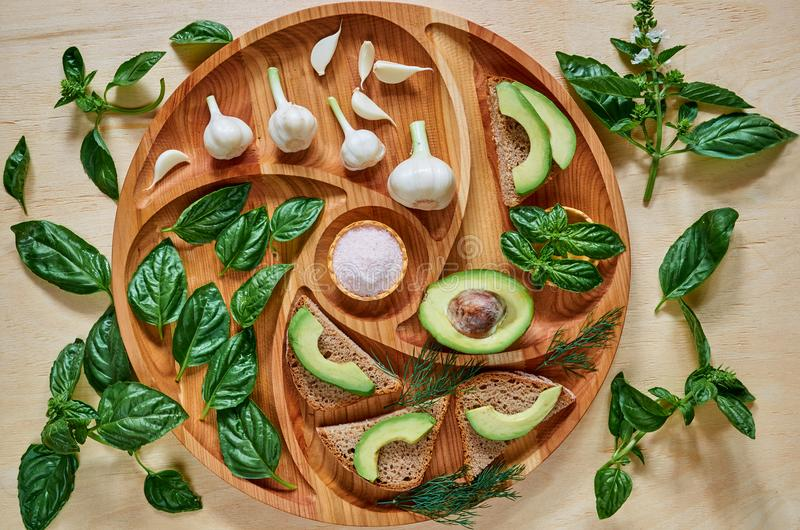Avocado toasts on the wooden plate with garlic, basil, dill and salt. Vegan avocado sandwiches decorated with basil leaves. Ingredients for healthy breakfast stock images