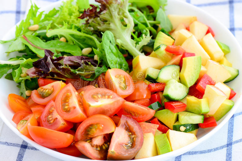 Avocado and tomato salad. Avocado cherry tomato zucchini salad with greens royalty free stock images