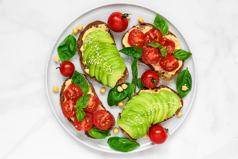 Avocado and tomatoes toasts with hummus, sesame and basil in a plate over white marble background. vegan food stock photos