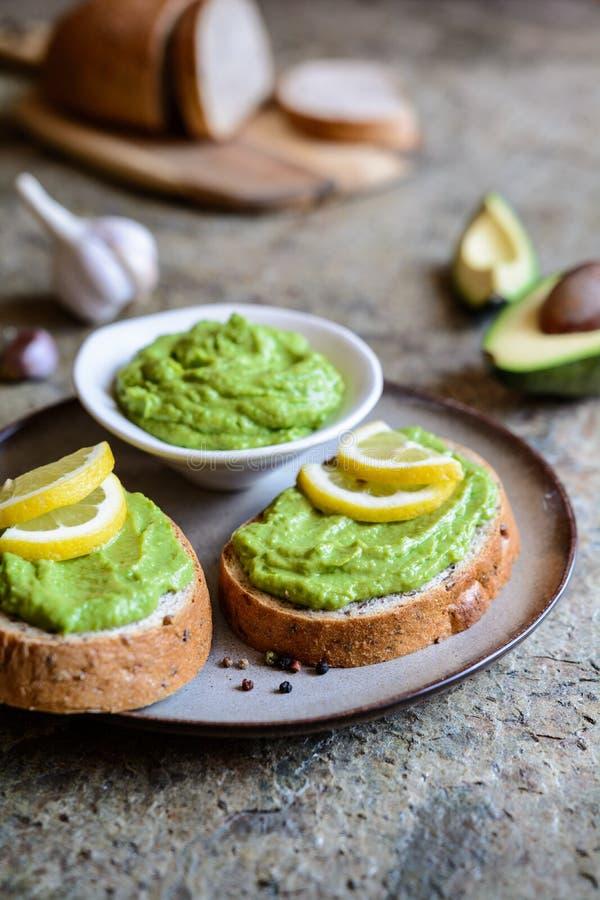 Avocado verbreitete mit Knoblauch auf Vollweizenscheibe brot stockfoto