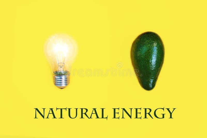 Avocado verde come fonte di energia vitale accanto ad una fine della lampadina su, su fondo giallo Sanità luminosa immagini stock libere da diritti