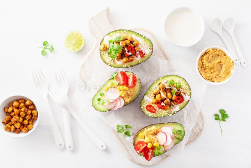 Avocadoboten met hummus, tomaten, radijs, geroosterde chi worden gevuld die royalty-vrije stock foto's