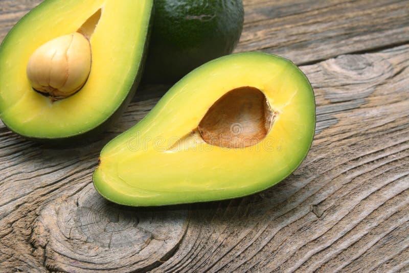 Avocados eine geschnitten in zwei mit Samen lizenzfreie stockfotografie