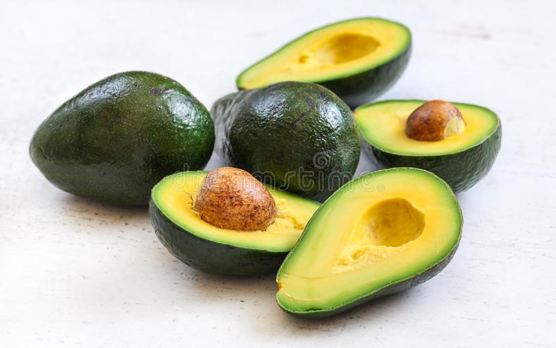 Avocados, ganz und halbiert - Samen sichtbar, auf weißem Arbeitsbrett stockfotografie