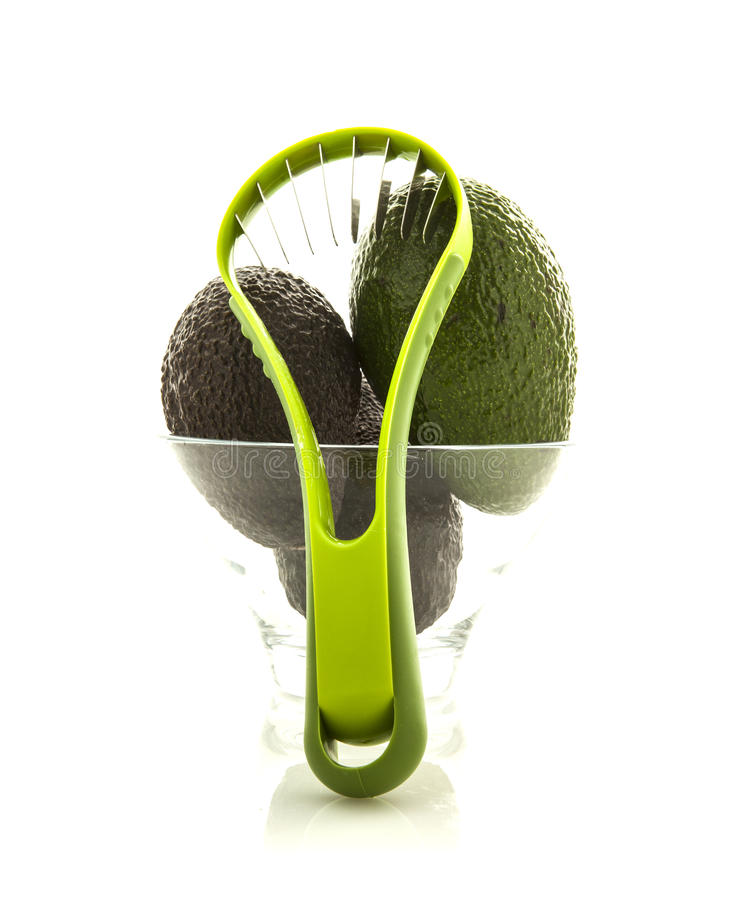 Avocados in glass bowl with slicer stock photo