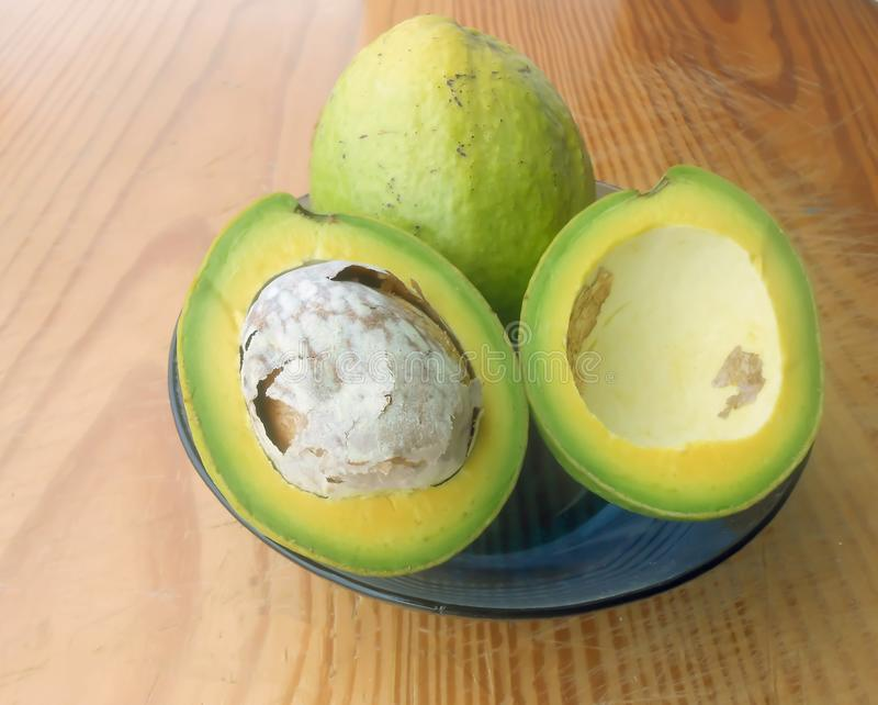 Avocados, Whole and Cross Section In A Dish. Two mature and ripe avocado pears in a blue dish sitting on a wooden surface. One cut in halves, with one half stock image