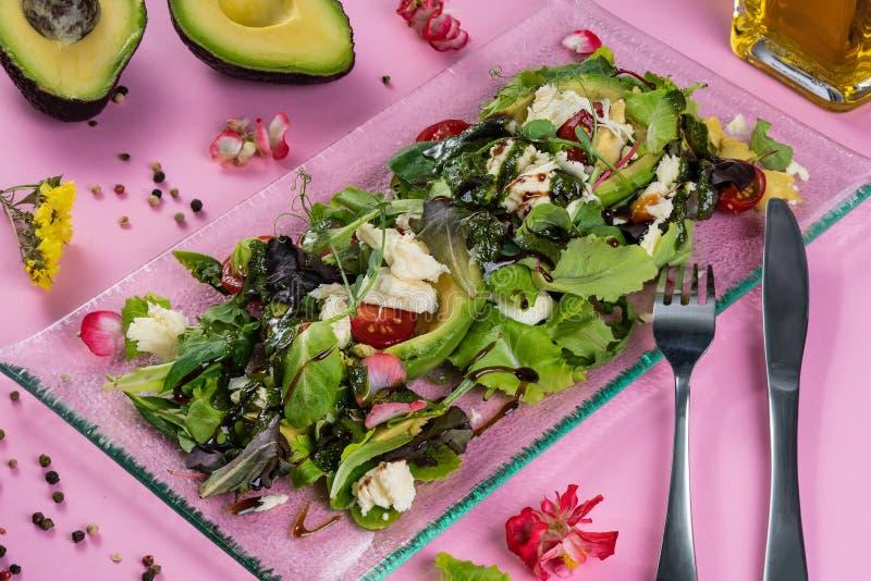 Avocadosalade met geitkaas, sla en saus Gediend op een lange transparante plaat met een vork en een mes stock foto's