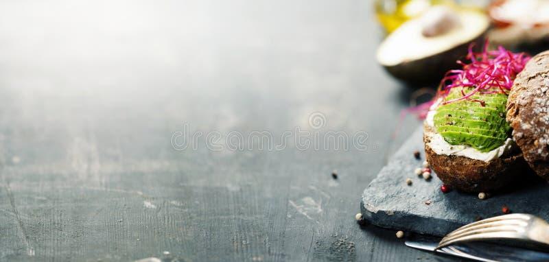 Avocadosandwich auf dem dunklen Roggenbrot gemacht mit neuem geschnittenem avocad stockbild