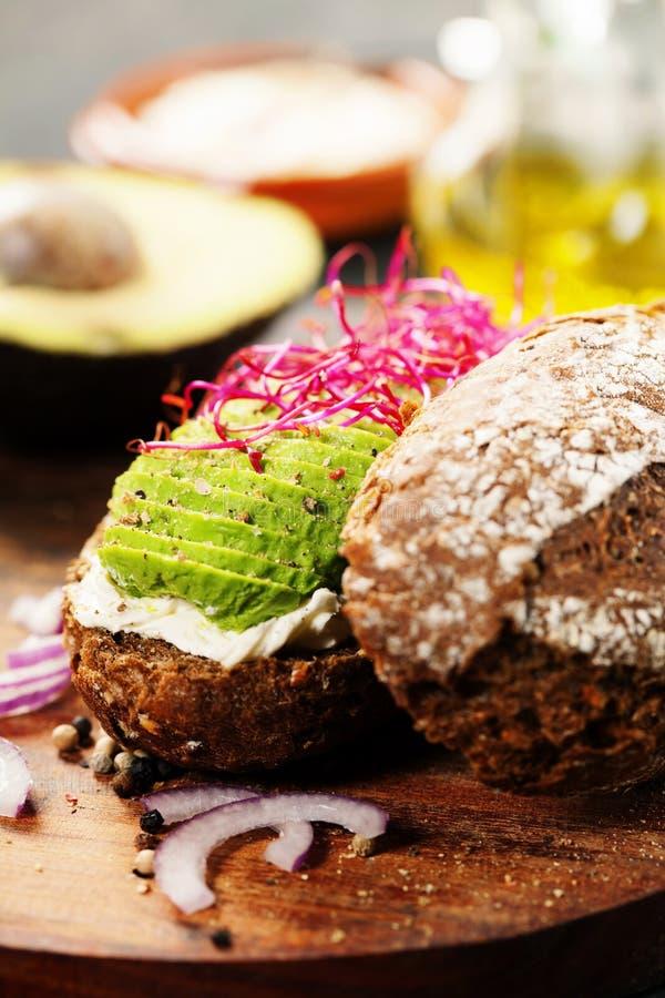 Avocadosandwich auf dem dunklen Roggenbrot gemacht mit neuem geschnittenem avocad lizenzfreies stockbild