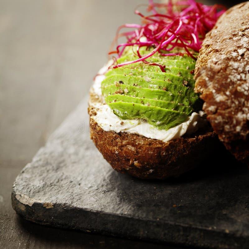 Avocadosandwich auf dem dunklen Roggenbrot gemacht mit neuem geschnittenem avocad stockfoto