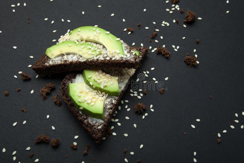 Avocadosandwich met sesamzaden en zwart brood dat op een zwarte achtergrond worden geïsoleerd royalty-vrije stock afbeelding