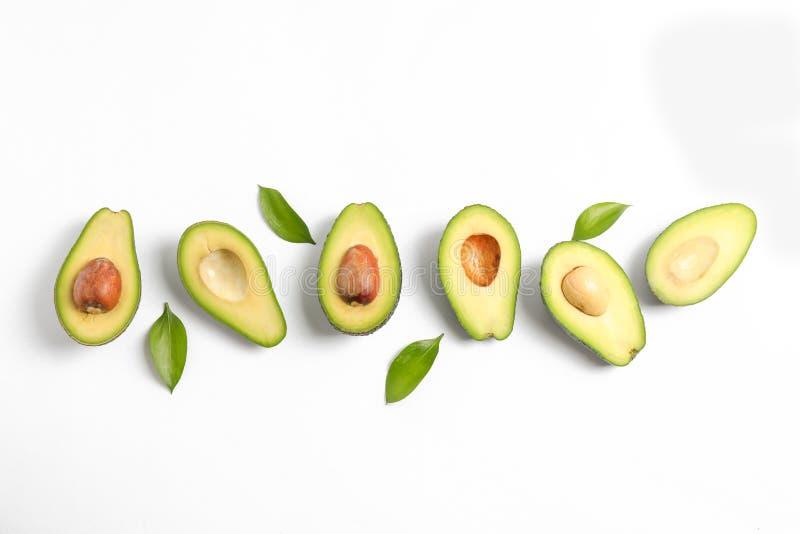 Avocat coupé en tranches mûr avec les feuilles vertes image libre de droits