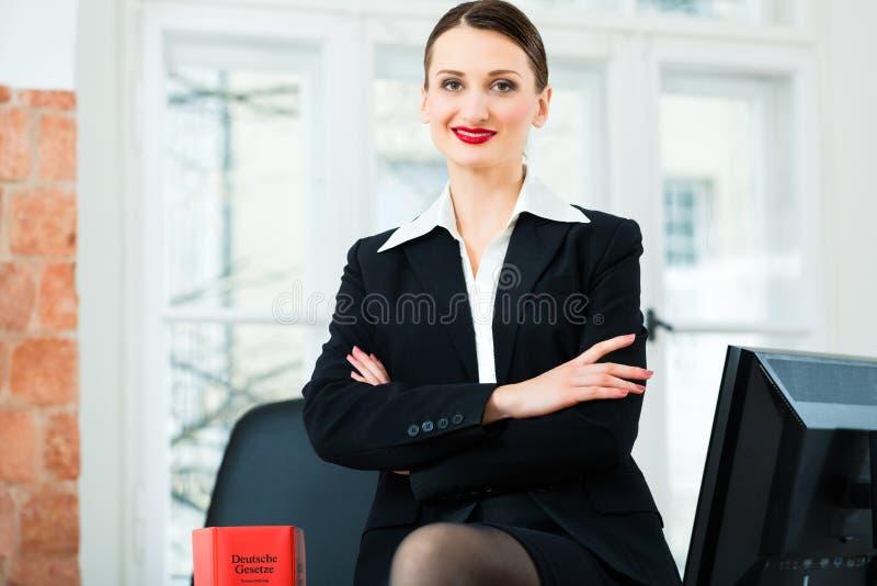 Avocat dans le bureau avec le livre de loi photographie stock