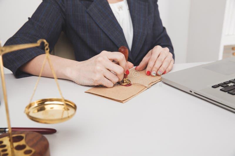 Avocat féminin dans le bureau se reposant et fonctionnant avec le papier et l'ordinateur portable image stock