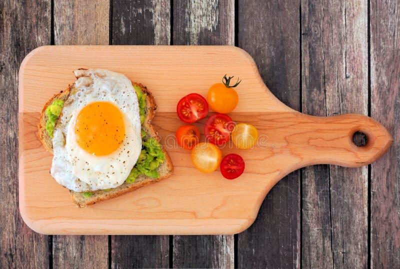 Avocat, pain grillé d'oeufs avec des tomates sur le panneau de palette photos stock