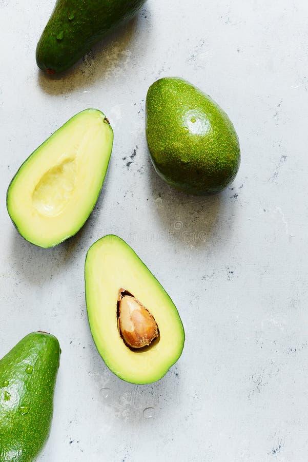 Avocat vert entier mûr sur un fond gris Configuration plate Concept de nourriture Vue supérieure Modèle vert d'avocats photos stock