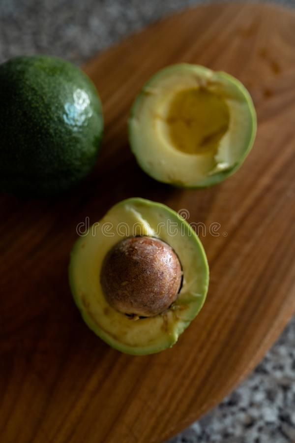 Avocats divisés en deux - vue supérieure de fruit frais obtenant la coupe sur un conseil photos stock