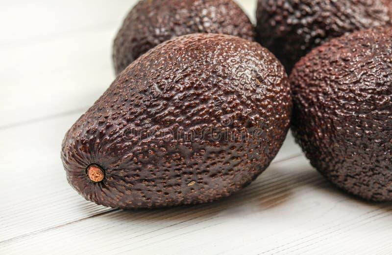 Avocats mûrs bruns foncés sur les conseils blancs Étroitement, détail sur la texture de peau évidente image stock