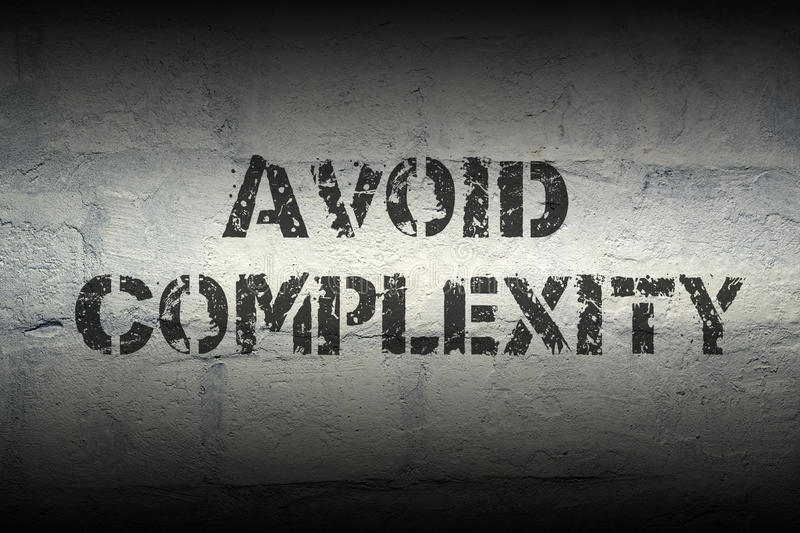 Avoid complexity GR. Avoid complexity stencil print on the grunge white brick wall; specially designed font is used stock photos