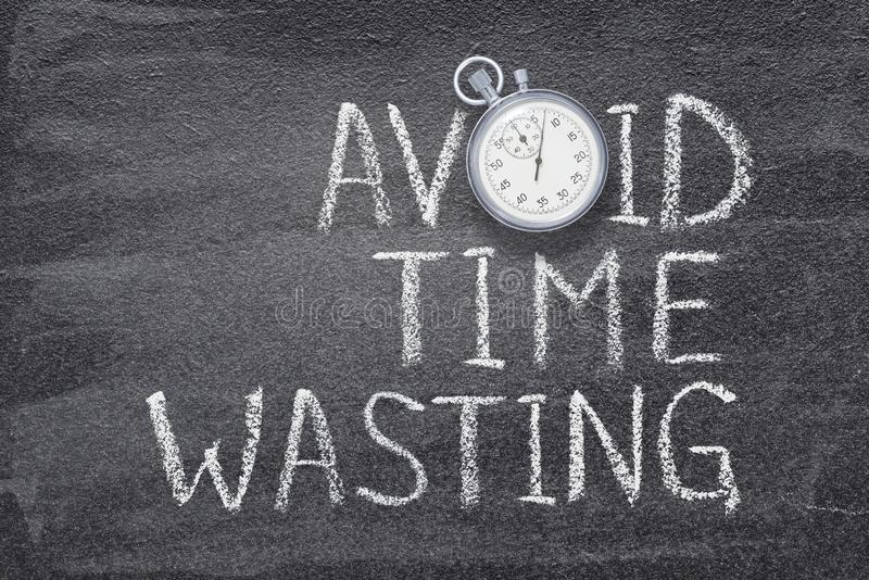 Avoid time wasting watch. Avoid time wasting phrase written on chalkboard with vintage precise stopwatch royalty free stock photo