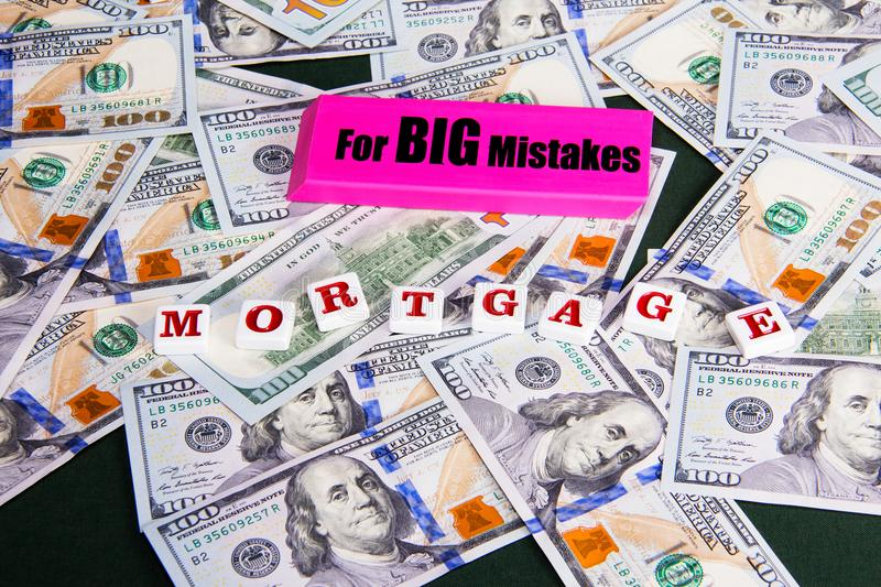 Mortgage: Avoiding mistakes when getting a home mortgage. Eraser and mortgage spelled out; covering hundred dollar bills. stock photos