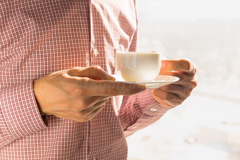 Avoir la tasse de café de matin près de la fenêtre photo stock