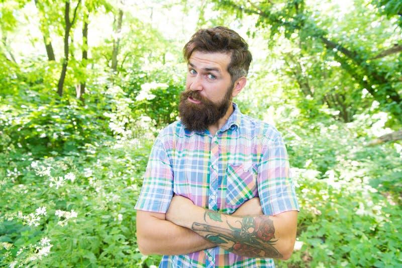 Avoir un tatouage très intéressant Hippie brutal gardant les bras croisés avec le tatouage sur le paysage d'été Type caucasien photos stock