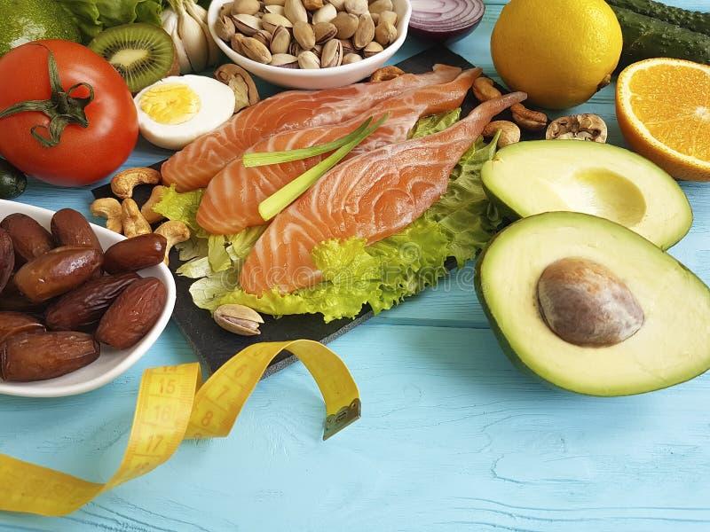 Avokado för omega 3 för cm för föda för citron för sallad för fisklaxdatum vård- på sund mat för blå träbakgrund royaltyfria foton