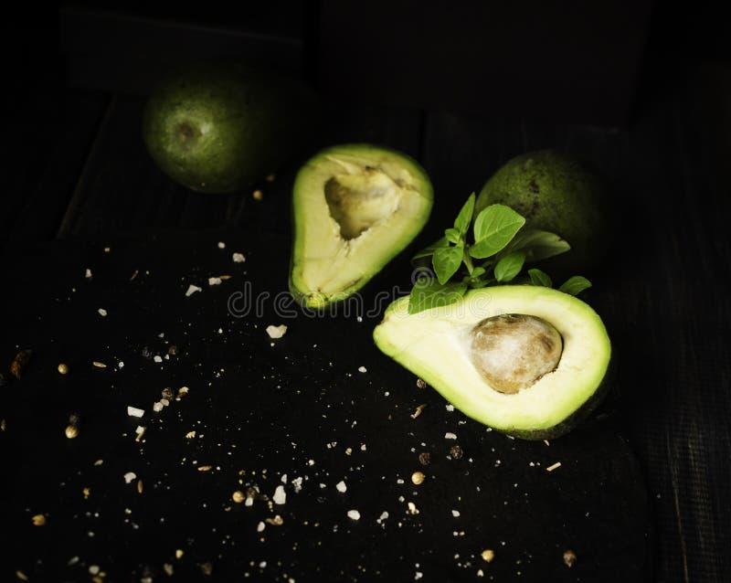 Avokado och kryddor på den svarta trätabellen med frukter, selektiv fokus, begrepp arkivfoton