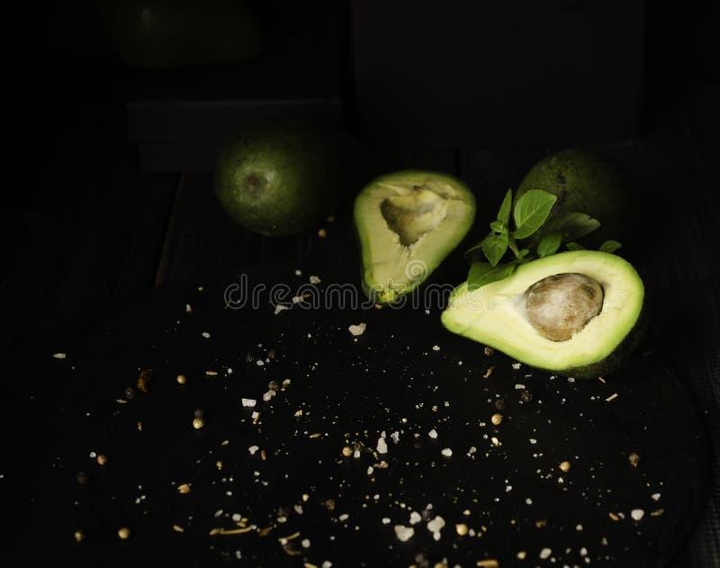 Avokado och kryddor på den svarta trätabellen med frukter, selektiv fokus, begrepp royaltyfri fotografi