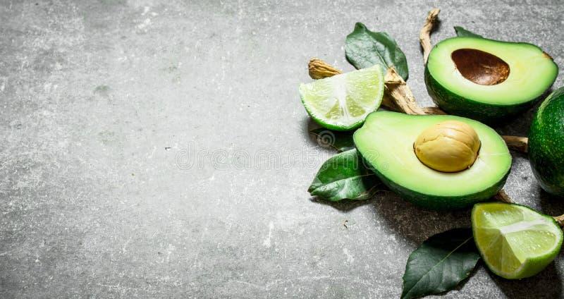 Avokado och limefrukt På stenbakgrund arkivfoton
