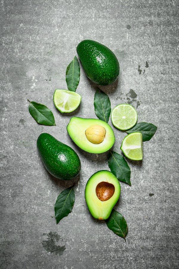 Avokado och limefrukt På stenbakgrund arkivfoto