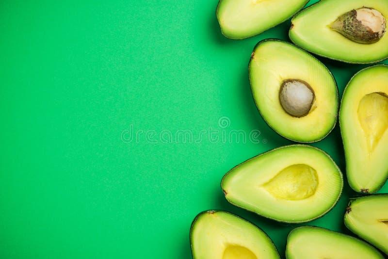 Avokado på pastellfärgad bakgrund, idérikt matbegrepp royaltyfri fotografi