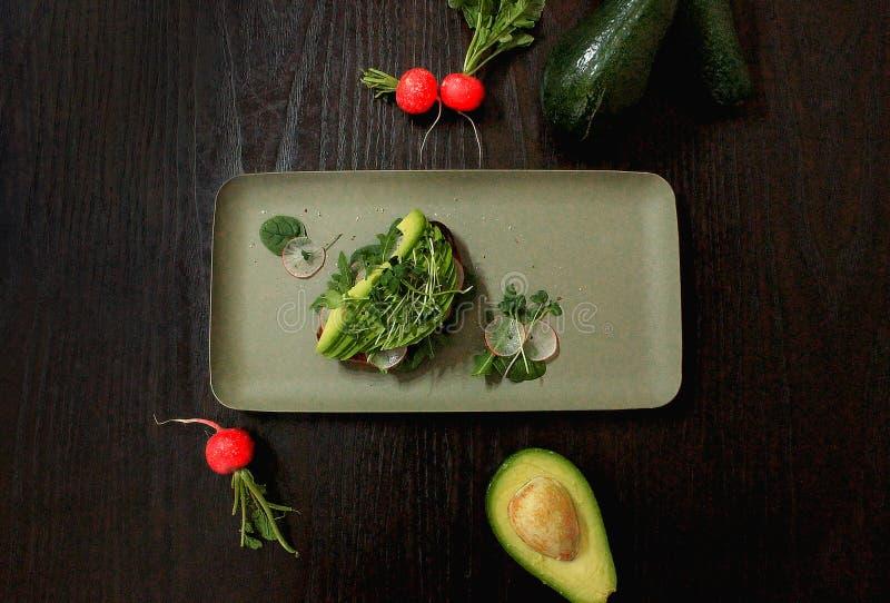 Avokado på rostat bröd och ingredienser för framställning det royaltyfri fotografi