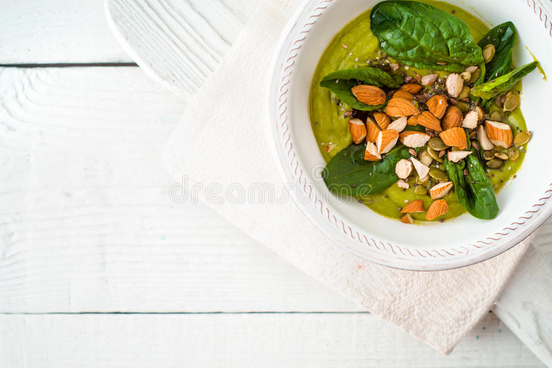 Avokadokräm med mandeln och spenat på den vita träbästa sikten för tabell arkivfoton