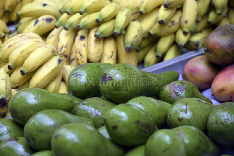Avokadon med bananer i bakgrunden i öppen luft marknadsför arkivbilder