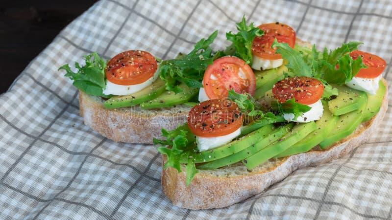 Avokadorostade bröd, körsbärsröda tomater på en träbakgrund Frukostera med rostat bröd och avokadot, vegetarisk kokkonst, begrepp arkivfoto