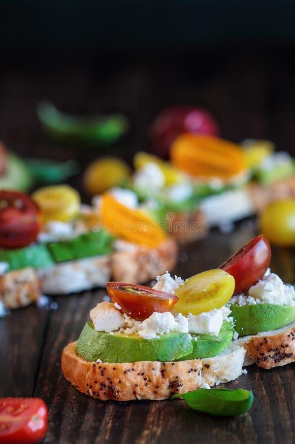 Avokadorostat bröd med avokadotomater basilika och Fetaost royaltyfri foto
