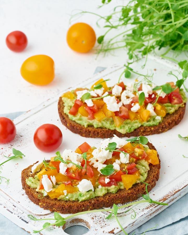 Avokadorostat bröd med feta och tomater, smorrebrod med ricotta, closeup och lodlinje arkivfoton
