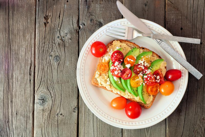 Avokadorostat bröd med hummus och tomater, ovanför sikt på trä royaltyfri fotografi