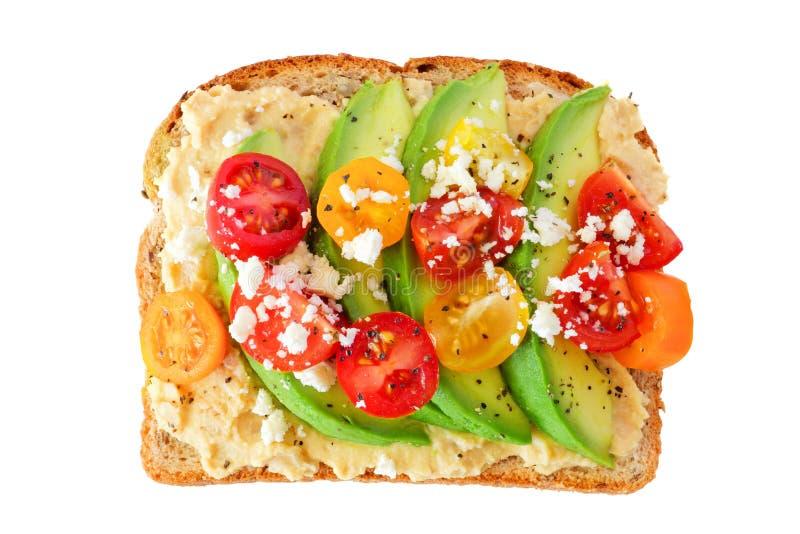 Avokadorostat bröd med hummus och tomater som isoleras på vit arkivfoto