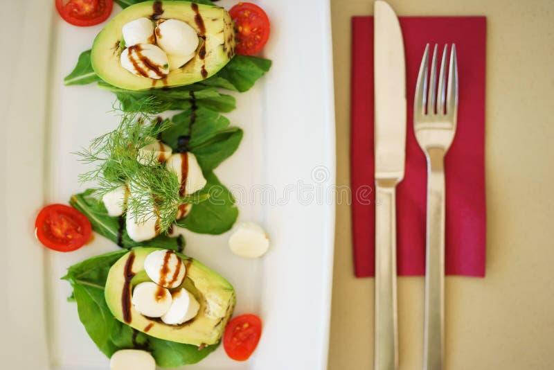 Avokadosallad med mozzarellaost, körsbärsröda tomater, örter och sås i en platta på tabellen i en restaurang royaltyfri fotografi