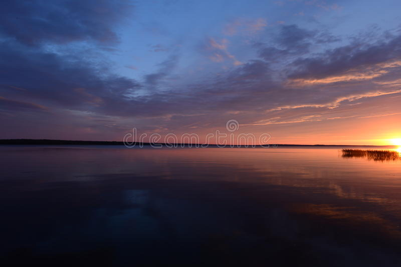 Avondhemel bij zonsondergang over de meerwaterspiegel stock afbeeldingen