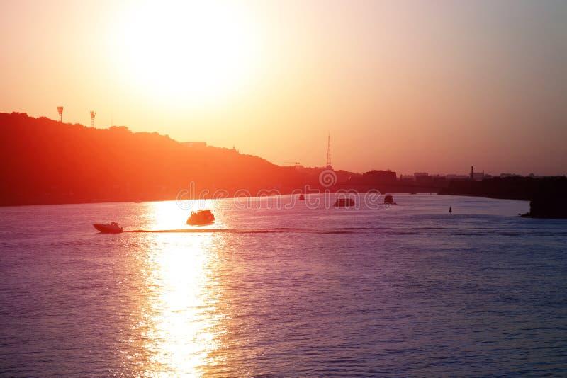 Avondlandschap met rivier en boten stock foto