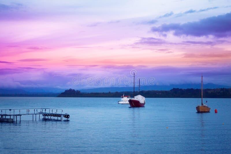 Avondoceaan met boten en kustlijn stock afbeeldingen